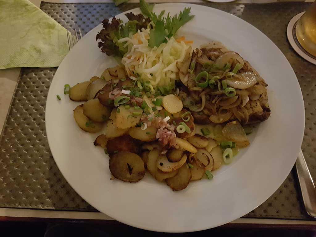 Weißiger Rostbrät´l, ein Schweinekamm unter einer Bier-Senf-Kruste, geschmorte Zwiebeln, Bratkartoffeln und Krautsalat für 9,50 €