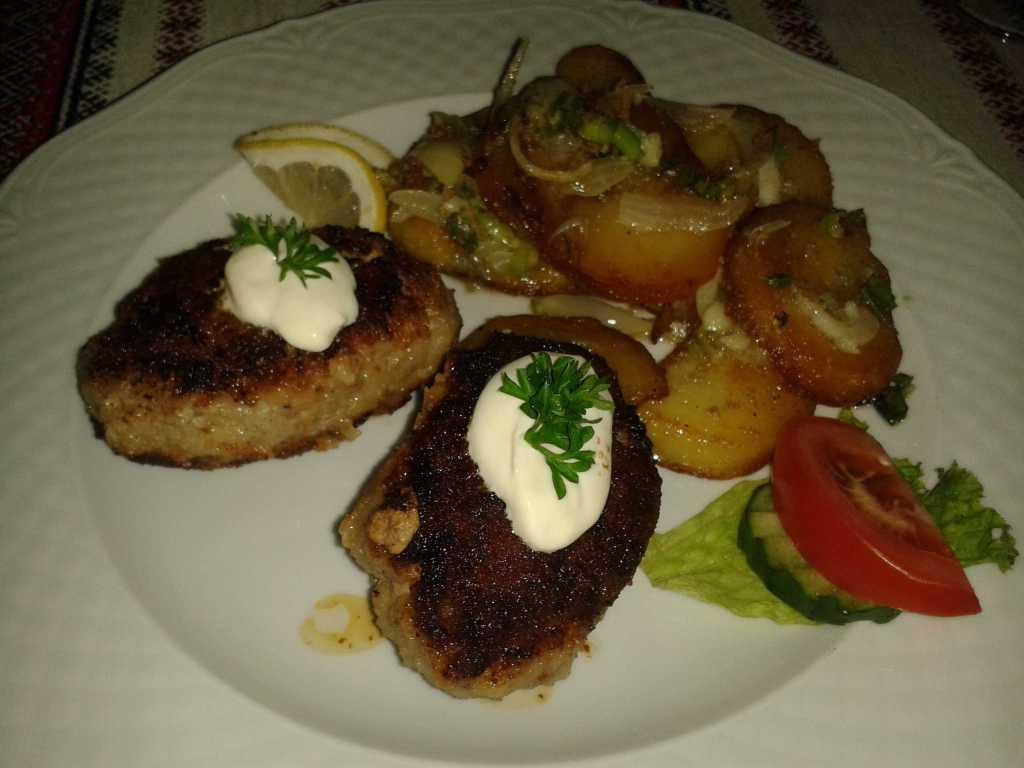 Russischen Buletten mit Knoblauch-Bratkartoffeln, dazu bunter Salat, gereicht mit 2 cl russischen Wodka