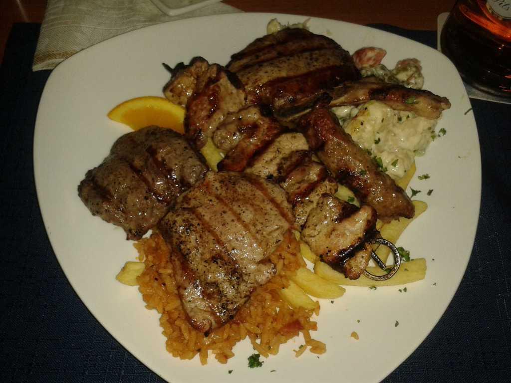 """""""Grillteller a la Chef"""" mit Schweinekotelett , Schweineschnitzelspieß, Cevapcici, Schweinemedallions, Rinderhüfte mit Djuwetschreis, Pommes Frites und ein kleiner Salat für 14,50 €"""
