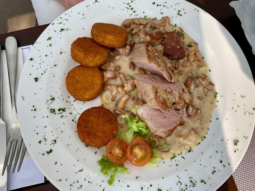 Am Stück gebratenes Schweinefilet auf Pfifferlingsrahmsauce mit Pommes Macaire und Salat