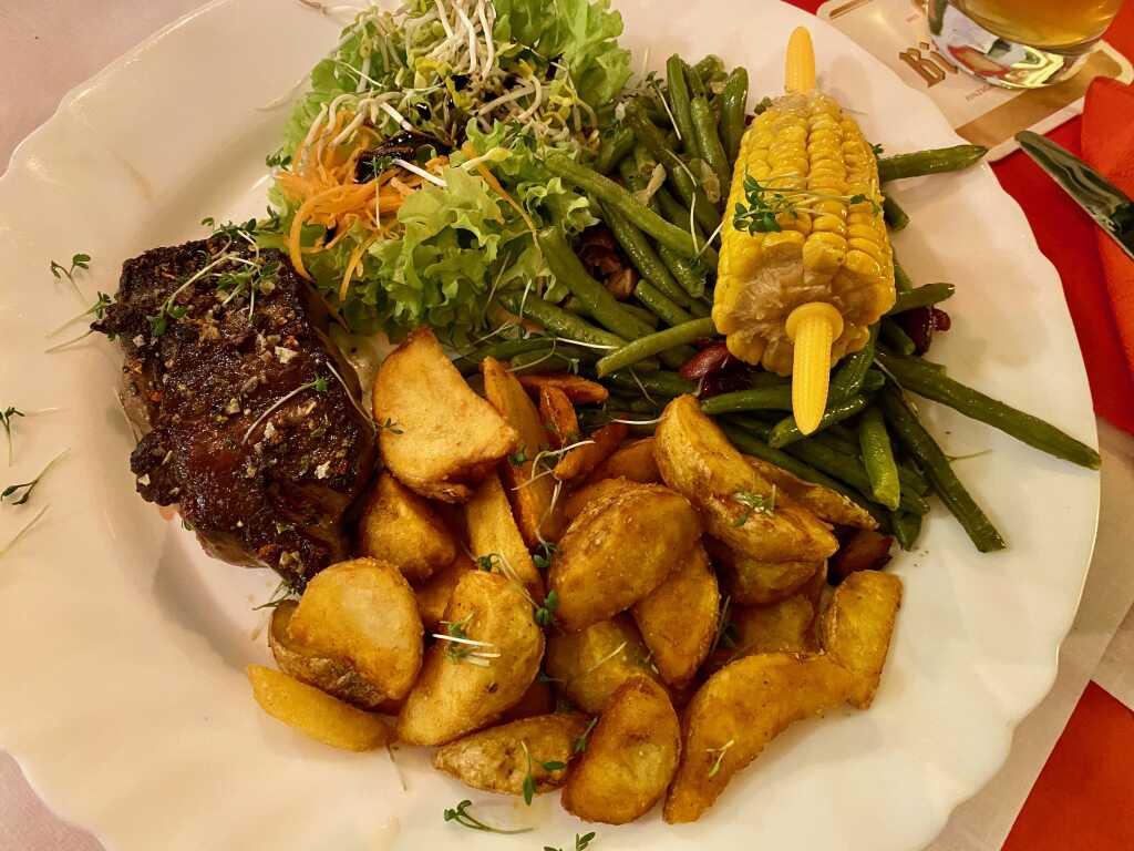 """Elchsteak """"Ontario"""" mit grünen Bohnen und Kidney-Bohnen, ein halber Maiskolben in Honigbutter gegart, dazu amerikanische Kartoffel-Wedges"""