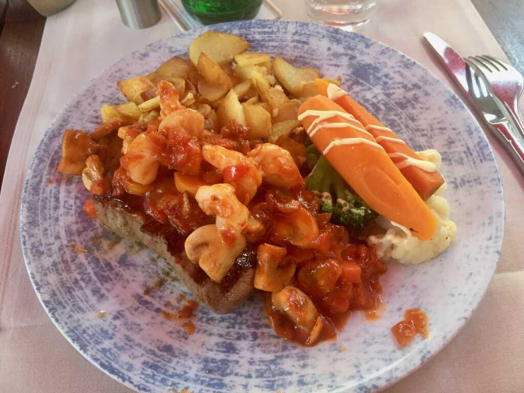 """Rumpsteak """"Diabolo"""" mit Garnelen und Champignons in teuflisch scharfer Sauce, dazu Gemüse und Bratkartoffeln mit Speck"""