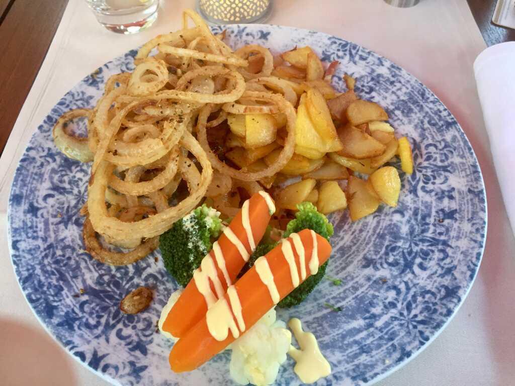 Zwiebelrostbraten, Hüftsteak mit gerösteten Zwiebeln, dazu Gemüse und Bratkartoffeln mit Speck