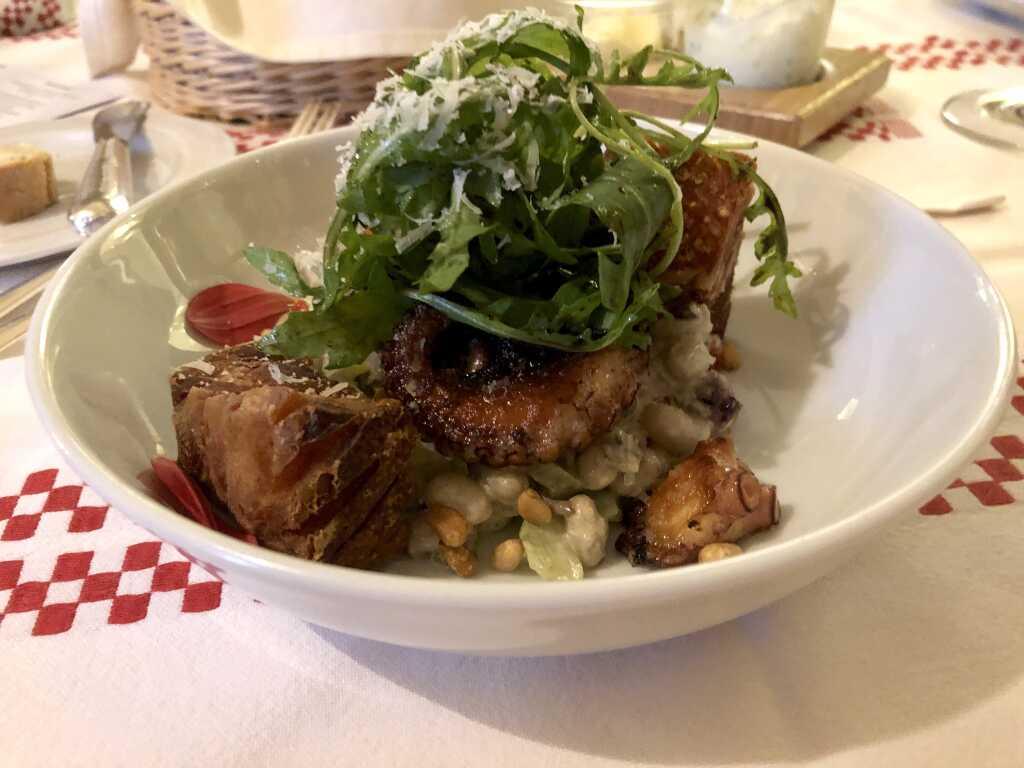 Weißer Bohnensalat mit getrockneten Tomaten, gegrilltem Pulpo, krossem Schweinebauch, Ruccola, Balsamico und Pinienkernen