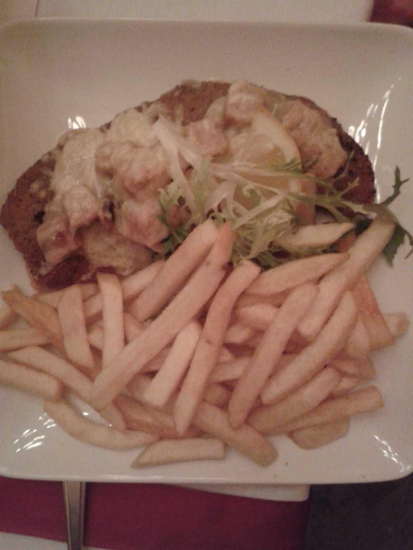 Schweineschnitzel au four-Schnitzel mit Würzfleisch überbacken, Buttererbsen und Pommes Frites für 13,80 €