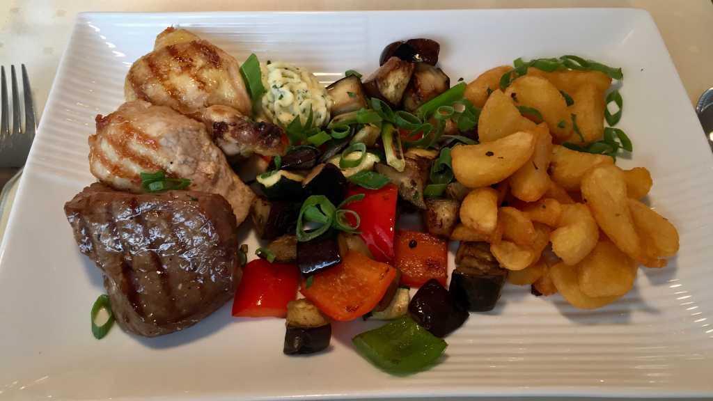 """Grillpfanne """"Euro Park Hotel"""" mit Rumpsteak, Maispoularde, Schweinesteak & Bacon, serviert mit Gemüse und hausgemachten Wedges"""