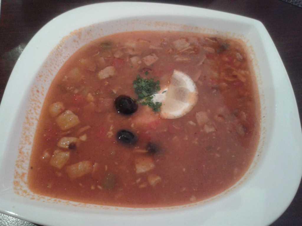 Soljanka (eine kräftig-würzige Suppe aus verschiedenen Fleischsorten und Salzgurken, serviert mit schwarzen Oliven, Zitronenscheibe und Smetana)