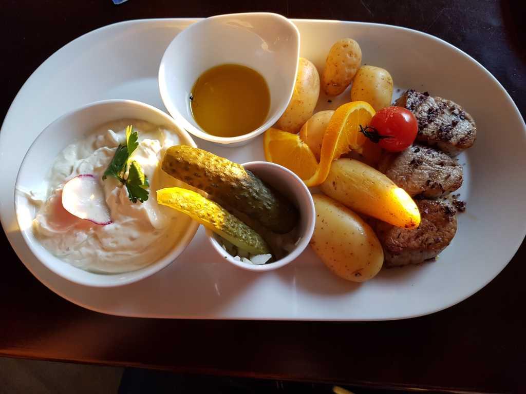 """den """"Möwenschiss""""-bestehend aus ungeschälten jungen Kartoffeln mit feinstem Kräuterquark, Lausitzer Leinöl, Spreewaldgurke und Zwiebeln, zusätzlich mit Schweinemedallions für 16,90 €"""