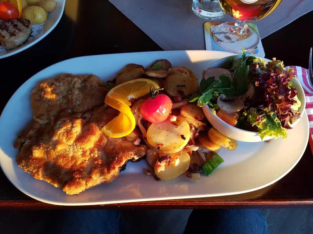 Riesenkotelett in einer Senf-Meerrettich-Panade, dazu goldbrauen Bratkartoffeln und bunter Salat für 15,90 €