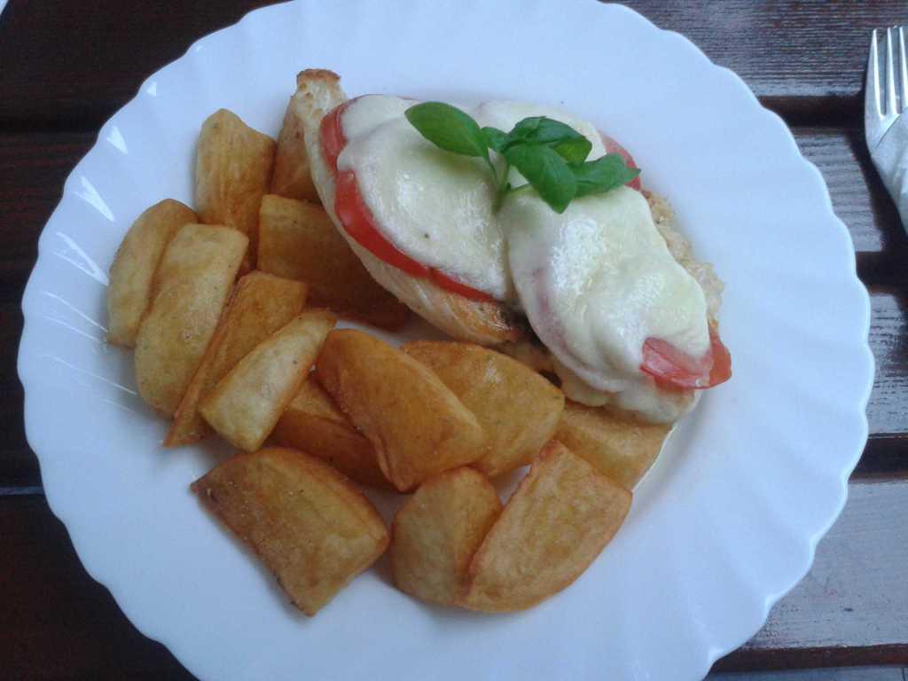 Zartes Hähnchenbrustfilet mit Tomate und Mozzarella überbacken, Petersilienpesto, dazu Rosmarinkartoffelnecken
