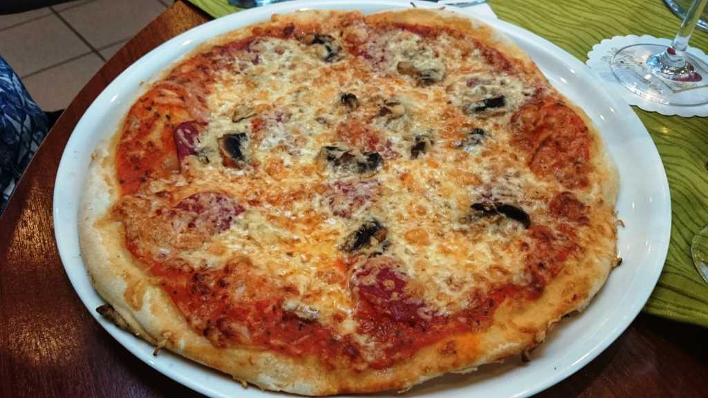 Pizza mit Salami und frischen Champingons