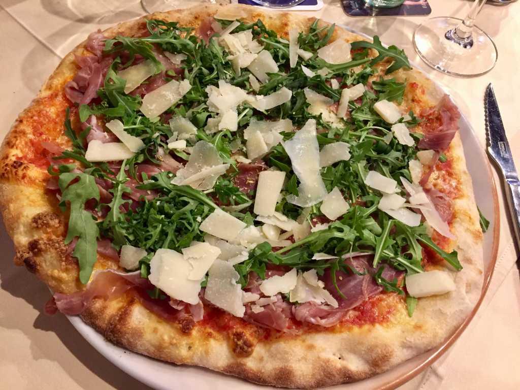 Pizza Mediterranea mit Parmaschinken, Parmesanhobel und Rucola