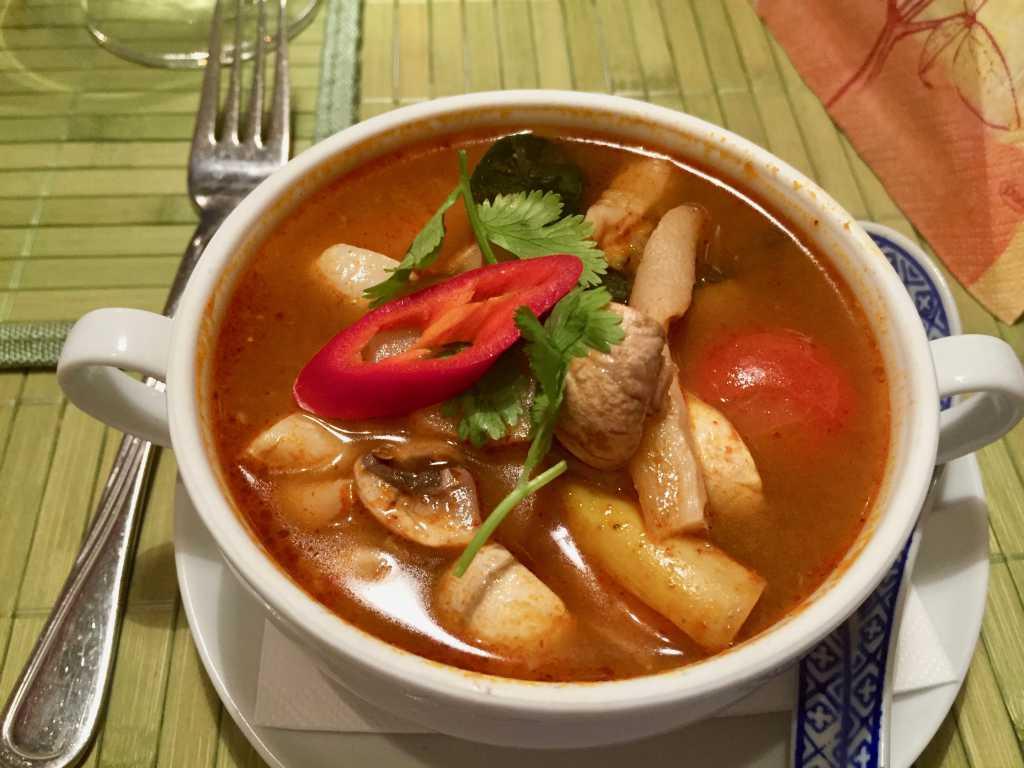Tom yam Plah, eine klare scharfe Suppe von Edelfischen mit Champignons, Zitronengras, Koriander, Limettenblättern und Cherrytomaten