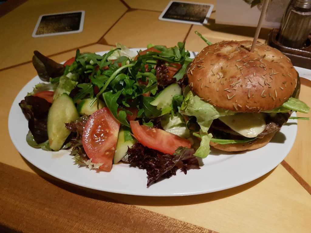 """""""Italian Burger""""- Saftig gegrillter Beef Burger im Focacciabrötchen, belegt mit Tomatenwürfeln und Zwiebeln in Olivenöl, Mozzarella, frischem Basilikum, Rucolasalat und Kräuter-Snacksauce, serviert mit buntem Salat und Balsamico Dressing für 9,00 €"""