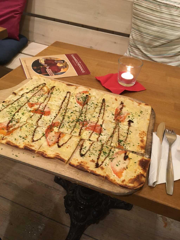 """Flammkuchen """"Italiano"""" mit Tomaten, Mozzarella, Zwiebeln, Balsamico-Creme und Emmentaler."""