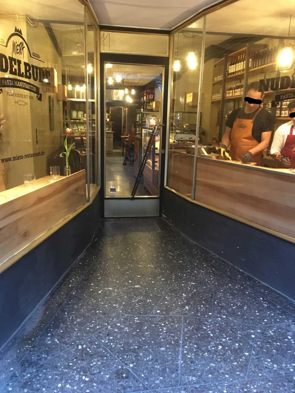 Außenansicht mit dem Eingangsbereich. Ganz hinten befindet sich die offene Küche, gleich vorne rechts die
