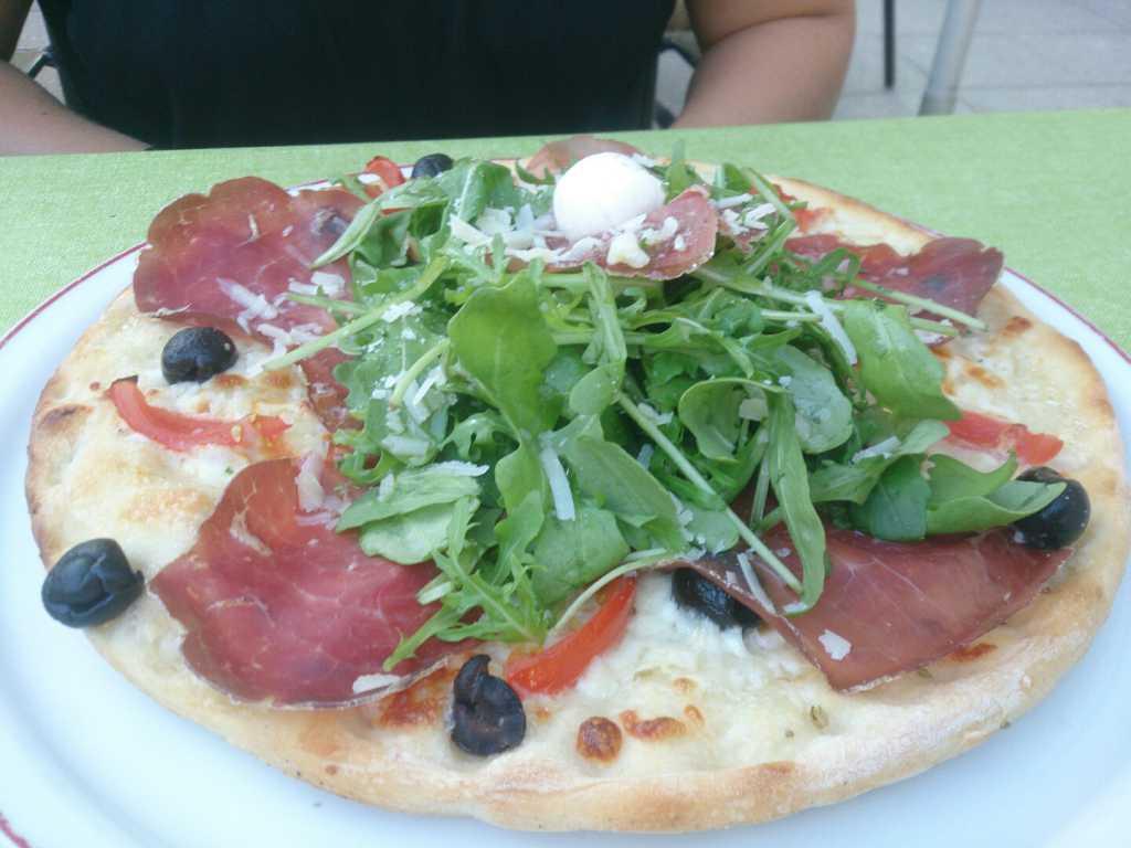 Pizza Bianca mit Büffelmozzarella, Bresaola, Rucola, Parmesan, Oliven und Kirschtomaten