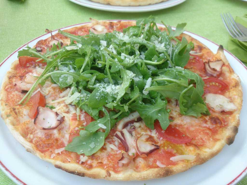 Pizza Margherita mit Pulpo, Schrimps, Knoblauch und Rucola